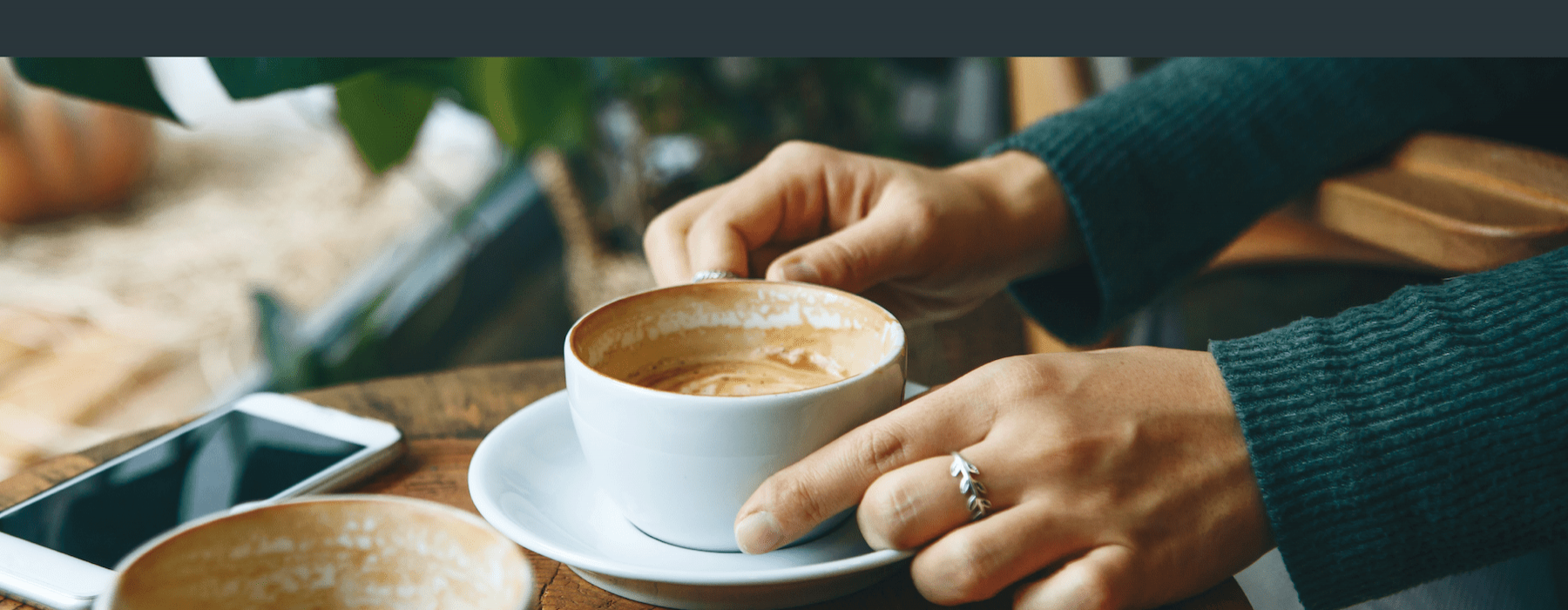 hands grabbing coffee from small wooden table.